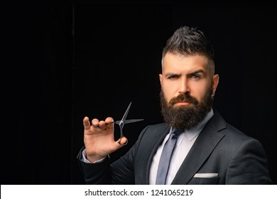 Bearded man, bearded hipster. Stylish man beard. Barber scissors. Vintage barbershop, shaving. Scissors in hand