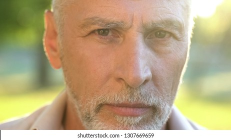 Bearded man in his 70s thinking about future and looking into camera, closeup