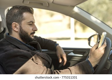 Bearded man in his car looking smartphone after parking while waiting