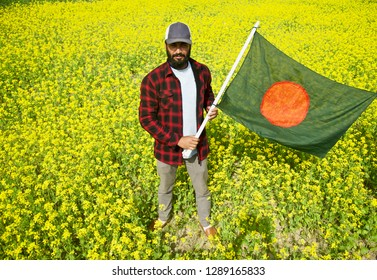 A bearded man holding the Bangladesh flag standing in a place