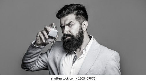 Bearded man holding up bottle of perfume. Man perfume, fragrance. Masculine perfume. Male fragrance and perfumery, cosmetics. Fashion cologne bottle. Bearded male prefers expensive fragrance smell.