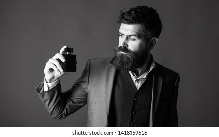 Bearded man holding up bottle of perfume. Fashion perfume bottle. Man perfume, fragrance. Perfume or cologne bottle. Male fragrance and perfumery, cosmetics. Black and white.