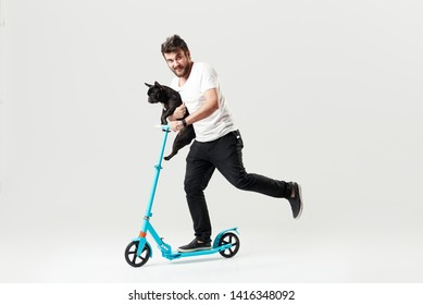 Bearded man holding a dog on electric scooter and riding it while feeling delighted. Full length portrait of an overjoyed guy riding a scooter and looking at the camera isolated on white background