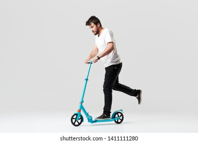 Bearded man holding the electric scooter and riding it while feeling delighted. Full length portrait of an overjoyed guy riding a scooter and looking at the camera isolated on white background