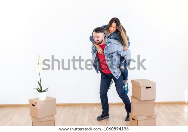 Bearded man holding a girl on his back with the keys to the new house on the background of cardboard boxes