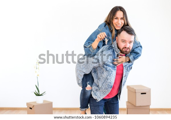 Bearded man holding a girl on his back with the keys to the new home