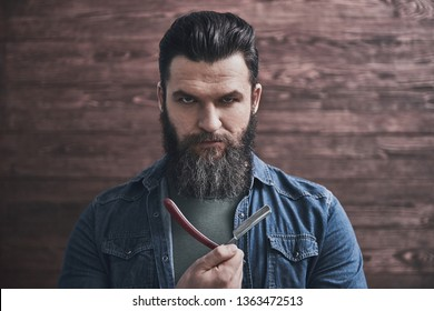 Bearded man is holding an old fashioned razor and looking seriously at camera, on wooden background
