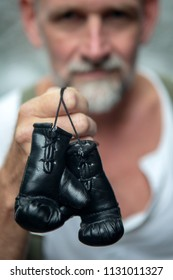 bearded man holding small toy boxing gloves in his hands