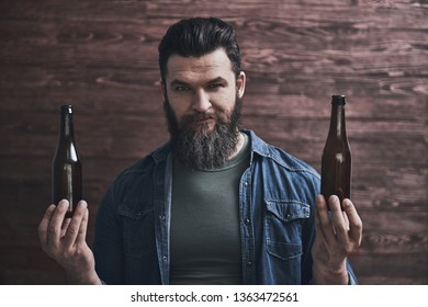 Bearded man is holding two bottles of beer, looking at camera and smiling, on a wooden background