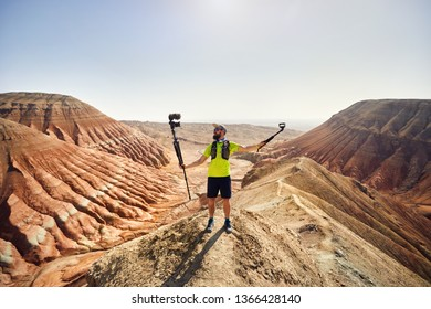 Bearded man holding two cameras on the top of the mountain in the desert