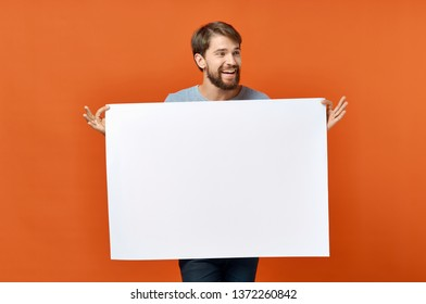 Bearded man holds in hands a white mockup Poster orange background