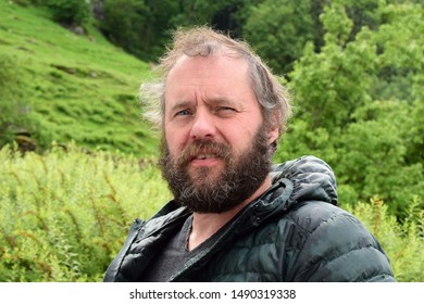 Bearded man in a jacket on a background of green hills. Cold summer in Norway