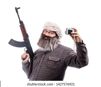 The bearded man with kalashnikov make selfie photo isolated on a white background. Funny warrior with automatic weapon smiling to camera.