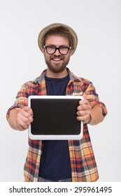 Bearded man keeping tablet PC in front of him. Man in straw hat and glasses big smiling in photostudio isolated on white.