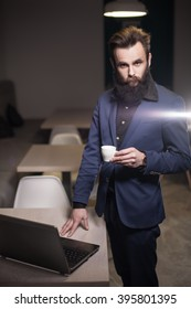 bearded man with laptop in cafe; young successful businessman with portable computer;