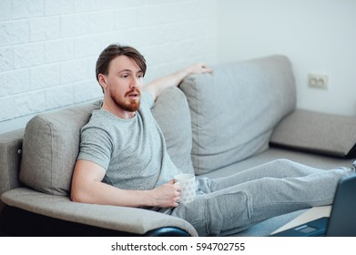 A bearded man with a laptop sitting on the sofa at home