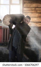bearded man with a large log in a wooden hut in the rays of dust, shavings and sunlight