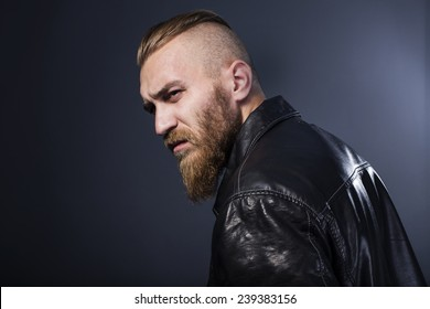 bearded man in leather jacket looking pensively into the distance