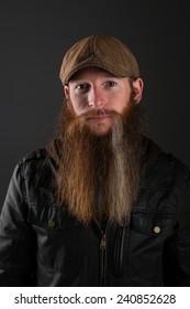 Bearded man in leather jacket wearing a cap.