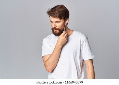 bearded man in a light T-shirt on a dark background
