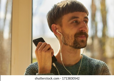 A bearded man is listening to music on headphones. The guy listens to music on headphones and enjoys.