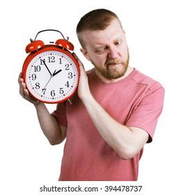 Bearded man listening to the ticking of alarm clock