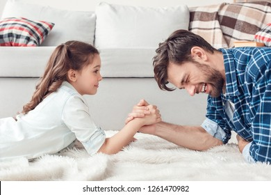 Bearded man and little girl at home family time lying on carpet on floor doing arm wrestling struggling having fun