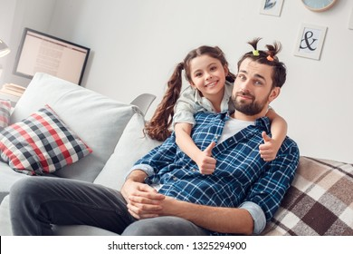 Bearded man and little girl at home family time sitting on sofa daughter hugging father having funny hairstyle looking camera smiling cheerful thumbs up