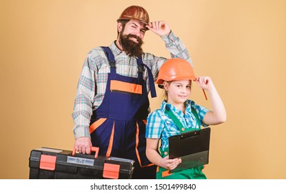 Bearded man with little girl. Repairman in uniform. Engineer. construction worker. Builder or carpenter. Repair. Childrens creativity. Father and daughter in workshop. Concentrated on your problem.