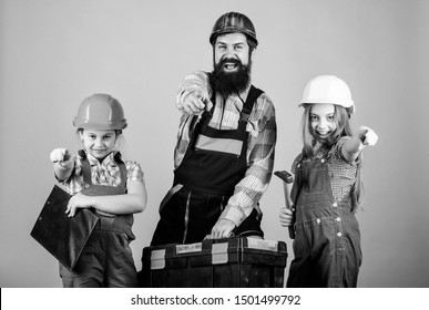 Bearded man with little girls. Father and daughter in workshop. Repairman in uniform. Foreman. construction worker assistant. Builder or carpenter. Family teamwork. Repair. Ready to start right now.