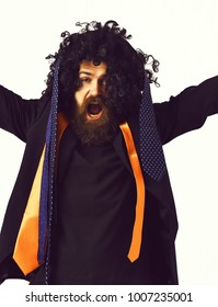 Bearded man, long beard. Brutal caucasian shouting hipster with moustache have colorful ties on suit and head with black curly afro wig isolated on white studio background