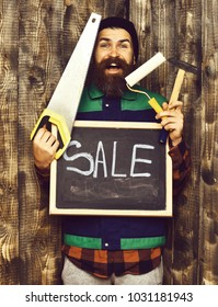 bearded man, long beard, brutal caucasian hipster with moustache holding various building tools: saw, hammer, roller paint, board with inscription sale, happy face on brown wooden background