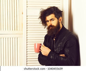 Bearded man, long beard. Brutal caucasian hipster with moustache and ruffled hair holding cup or mug in rock black style on white wooden vintage studio background