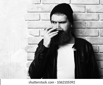 Bearded man, long beard. Brutal caucasian serious unshaven hipster smoking cigar with black leather jacket, hat and white shirt on beige brick wall studio background