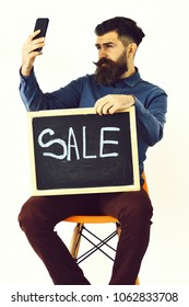Bearded man, long beard. Brutal caucasian serious hipster with moustache making selfie on cell phone and holding sale inscription on blackboard, sitting on the chair isolated on white background