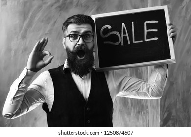 Bearded man, long beard. Brutal caucasian unshaven surprised hipster with glasses and moustache holding sale inscription on blackboard wearing white shirt, suede waistcoat on brown studio background