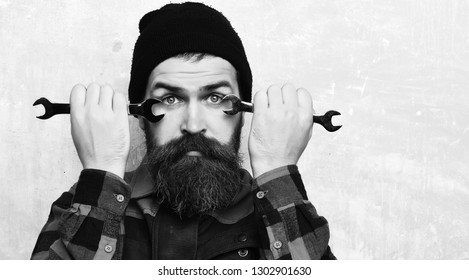 Bearded man, long beard. Brutal caucasian mechanic, surprised unshaven hipster in black hat, checkered shirt and uniform holding metallic wrenches on texture studio background