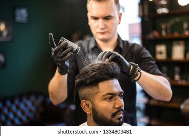 Bearded man with long beard, brutal, indian hipster with moustache, with stylish hair, haircut, getting powder on skin with make up brush by barber or hairdresser hands at barbershop