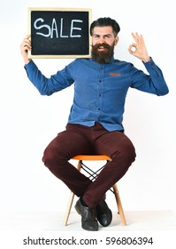 Bearded man, long beard. Brutal caucasian amused hipster with moustache holding sale inscription on blackboard, sitting on orange chair wearing blue shirt and vinous pants isolated on white background