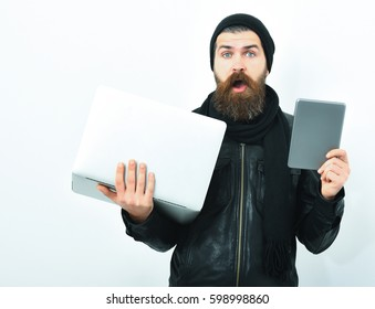 Bearded man, long beard. Brutal caucasian surprised unshaven hipster holding tablet and laptop in black leather jacket, hat and scarf isolated on white studio background
