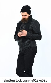 Bearded man, long beard. Brutal caucasian serious unshaven hipster holding cell phone in black leather jacket, hat and scarf isolated on white studio background