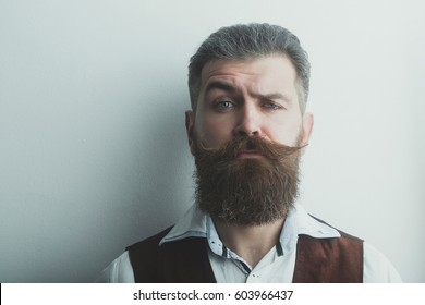 bearded man, long beard, brutal caucasian hipster with moustache with serious face in shirt and brown waistcoat on white background, unshaven guy with stylish hair getting haircut, copy space