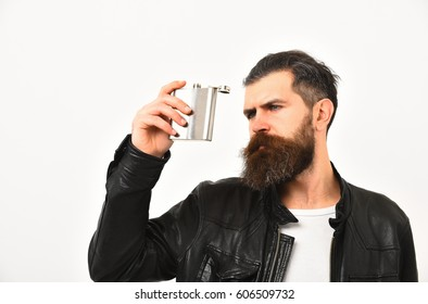 bearded man, long beard, brutal caucasian hipster with moustache holding metallic silver flask, jar for alcoholic drink, has serious face, in black leather jacket isolated on white background