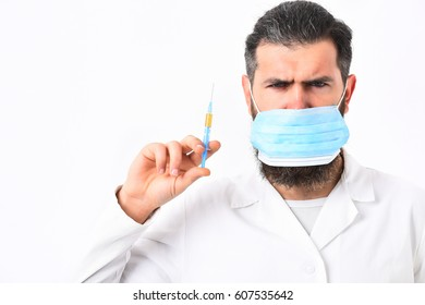 Bearded man, long beard. Brutal caucasian doctor or unshaven hipster, postgraduate student in mask and medical gown holding syringe isolated on white studio background. Medicine concept