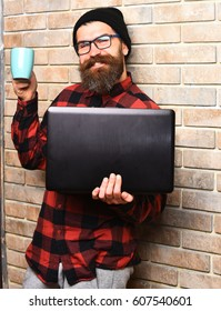 Bearded man, long beard. Brutal caucasian smiling happy unshaven hipster holding laptop with mag or cup in red black checkered shirt with hat and glasses on beige brick wall studio background