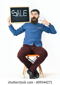 Bearded man, long beard. Brutal caucasian surprised hipster with moustache holding sale inscription on blackboard, sitting on orange chair wearing blue shirt, vinous pants isolated on white background