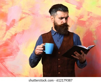 Bearded man, long beard. Brutal caucasian serious hipster with moustache holding blue coffee cup and black notebook in vintage shirt and leather vest on colorful studio background