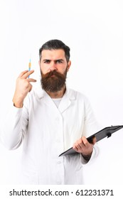 Bearded man, long beard. Brutal caucasian doctor or unshaven hipster, postgraduate student holding clipboard with syringe in medical gown isolated on white studio background. Medicine concept
