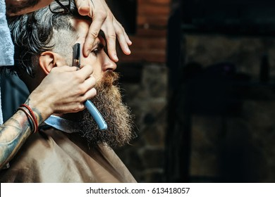 Bearded man with long beard, brutal, caucasian hipster with moustache, getting stylish hair shaving, haircut, with razor by barber or hairdresser with tattoo on hands at barbershop