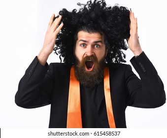 Bearded man, long beard. Brutal caucasian hipster with moustache have acid orange tie on suit and black curly afro wig isolated on white studio background